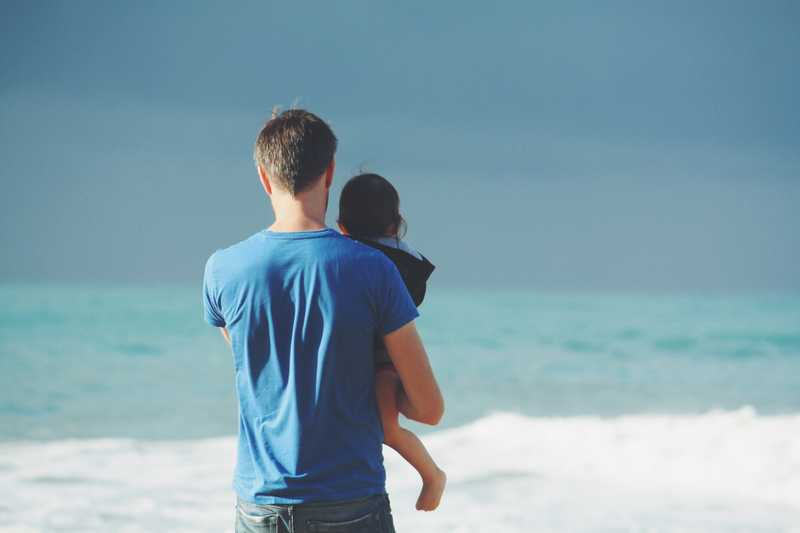 Photo of a father holding his child for PolicyMe's article on life insurance for children