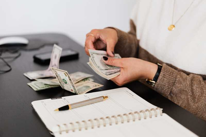 A woman sitting at a desk demonstrates financial responsibility by counting her cash and recording the balance in her note book