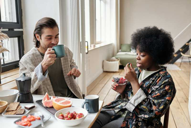 a man and a woman sit down together at a kitchen table to eat breakfast
