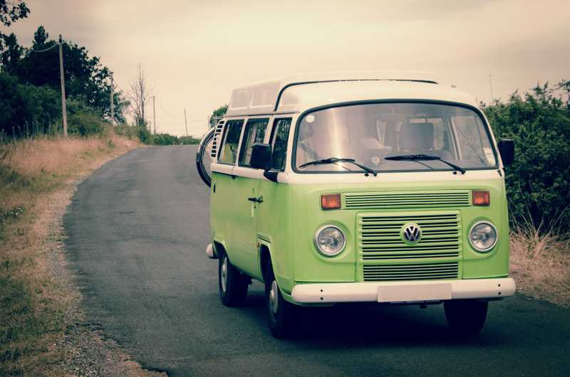 Photo of a Volkswagon bus driving down a rural road for PolicyMe's article of how you can save money on car insurance