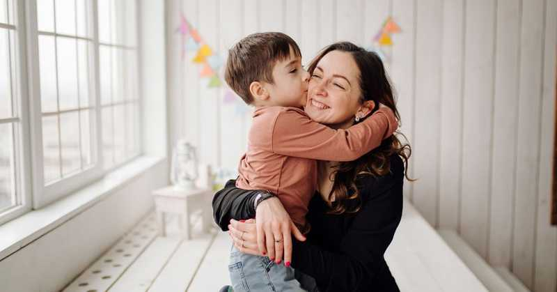child hugging mother by a window