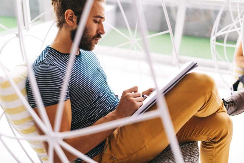 Photo of a man sitting and writing in a journal for PolicyMe's article on life insurance premiums