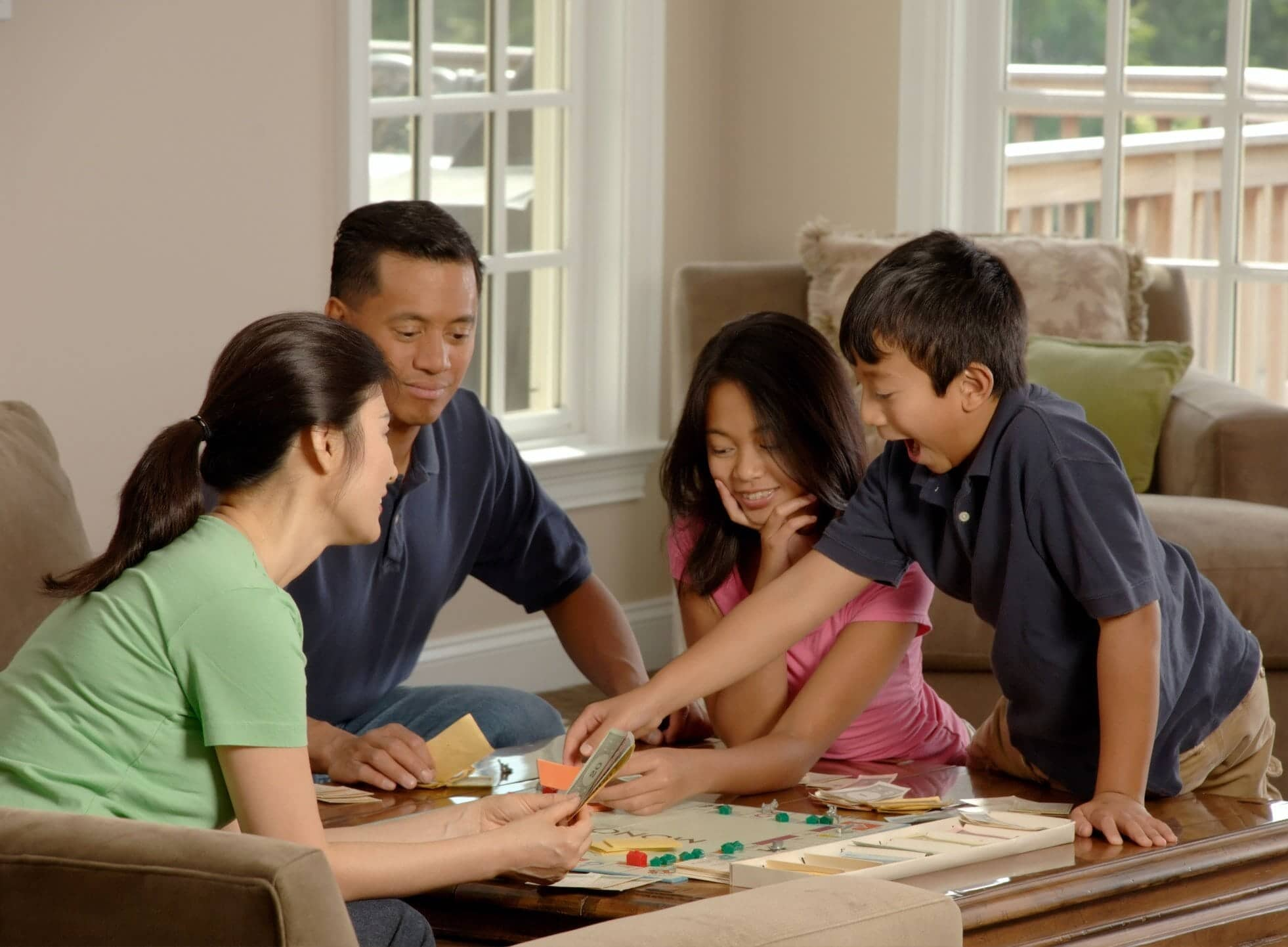 Family playing board game together for article answering the question How Does Term life Insurance Work