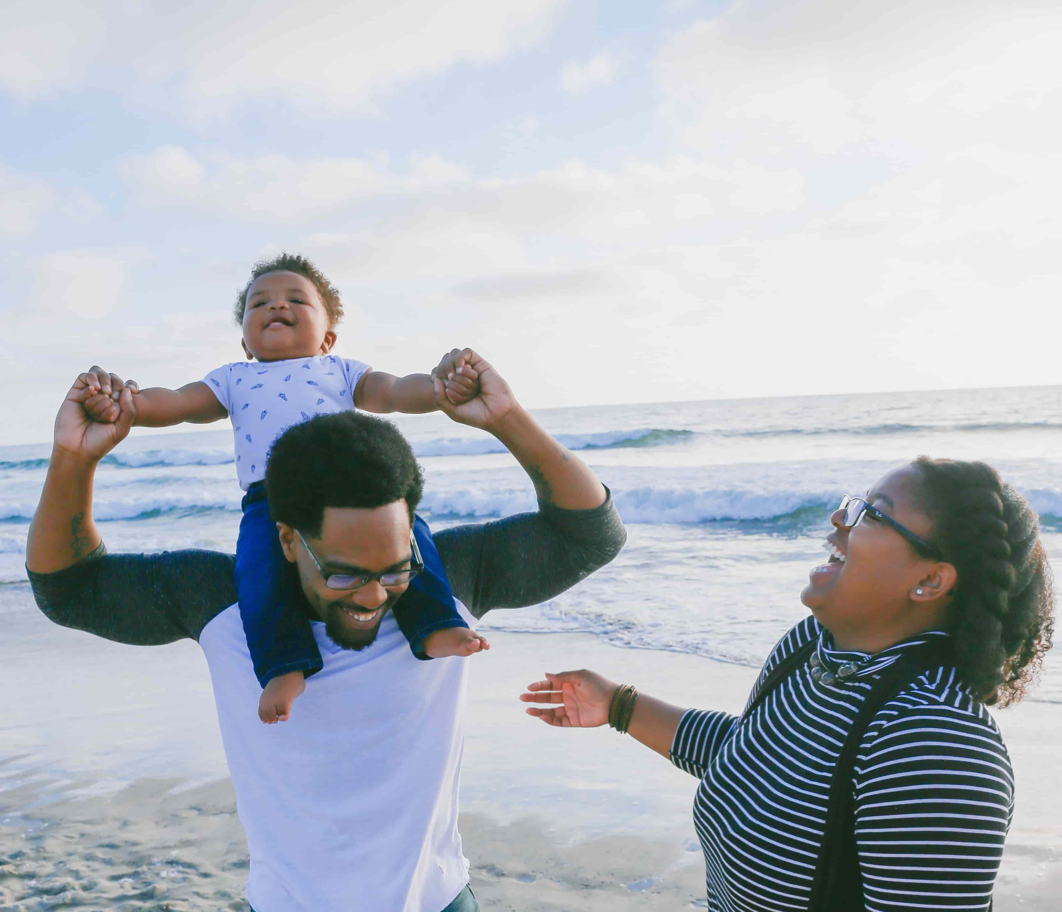 Father holding child on shoulders with mother laughing beside them on beach for article answering the question How Does Term Life Insurance Work