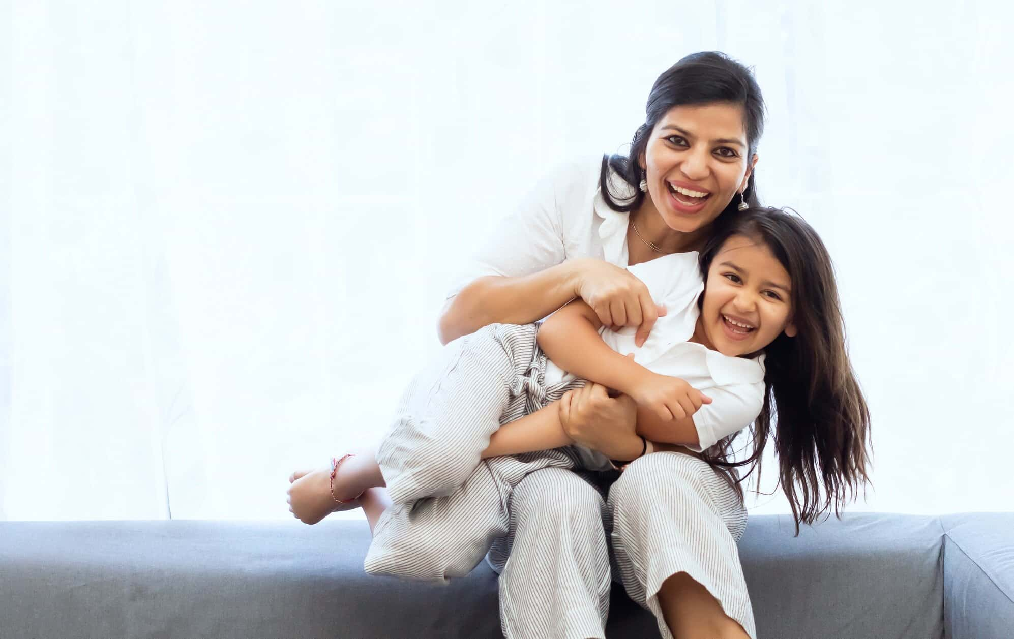 Mother holding daughter, both smiling at camera for article about term life insurance