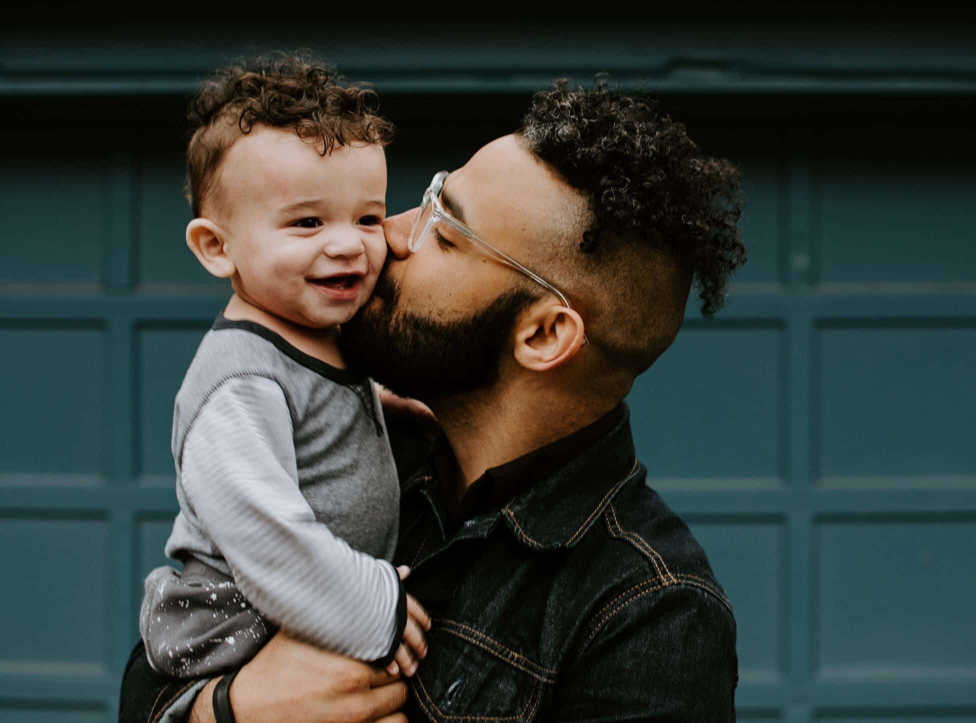 Father kissing cheek of smiling child for article about term life insurance