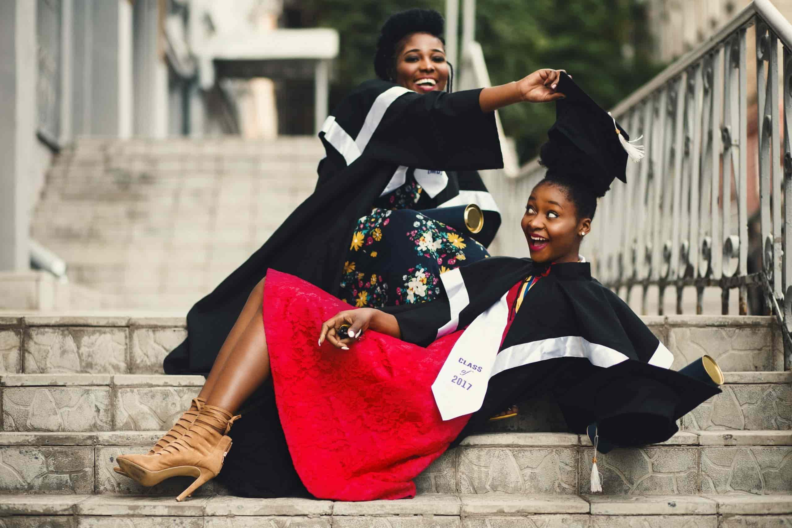 Photo of two women in graduation gowns on stairs, smiling, for page on Life Insurance Reviews