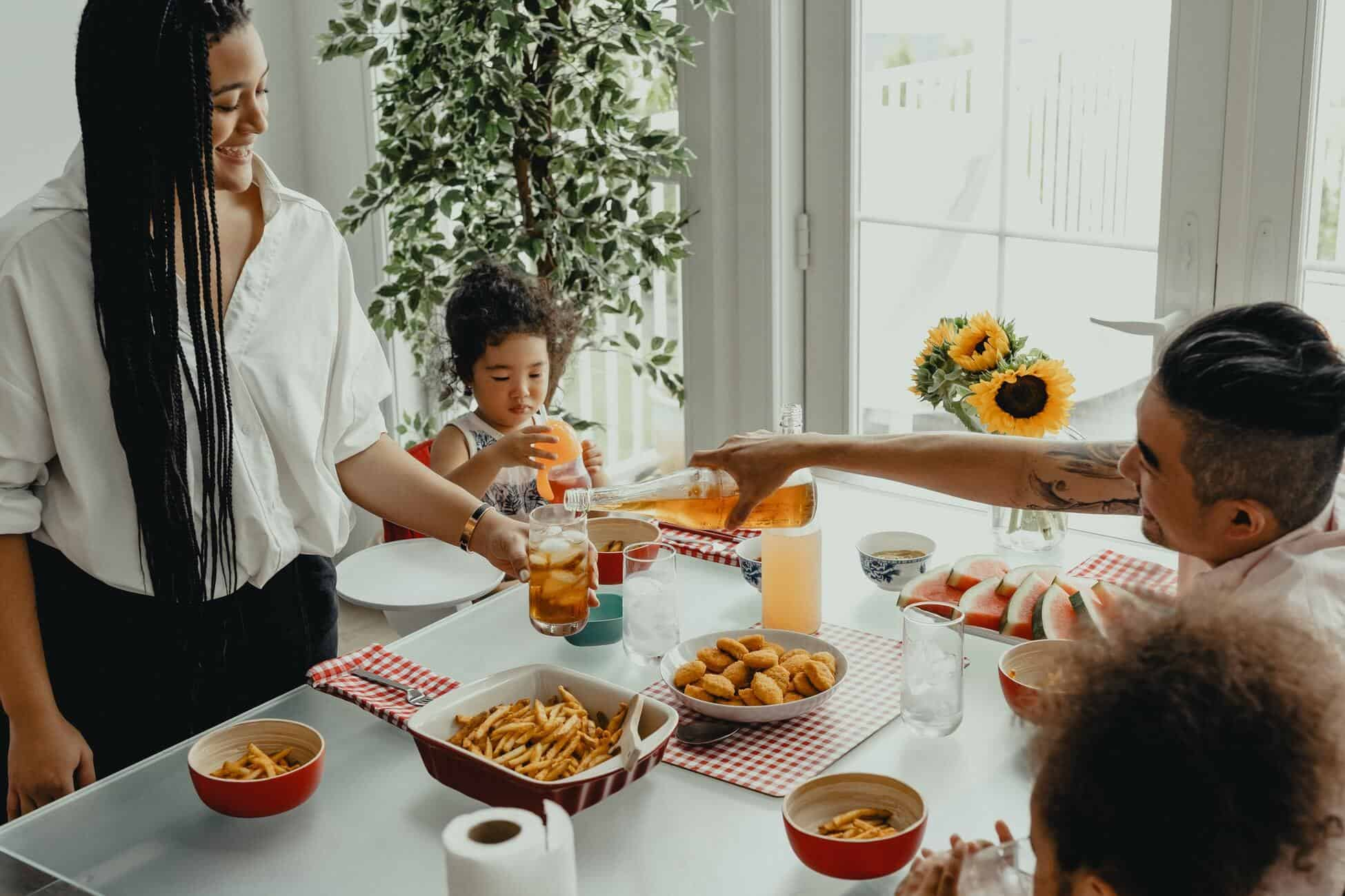 Image of family serving lunch at the dinner table for article about How Much Life Insurance Do I Need?