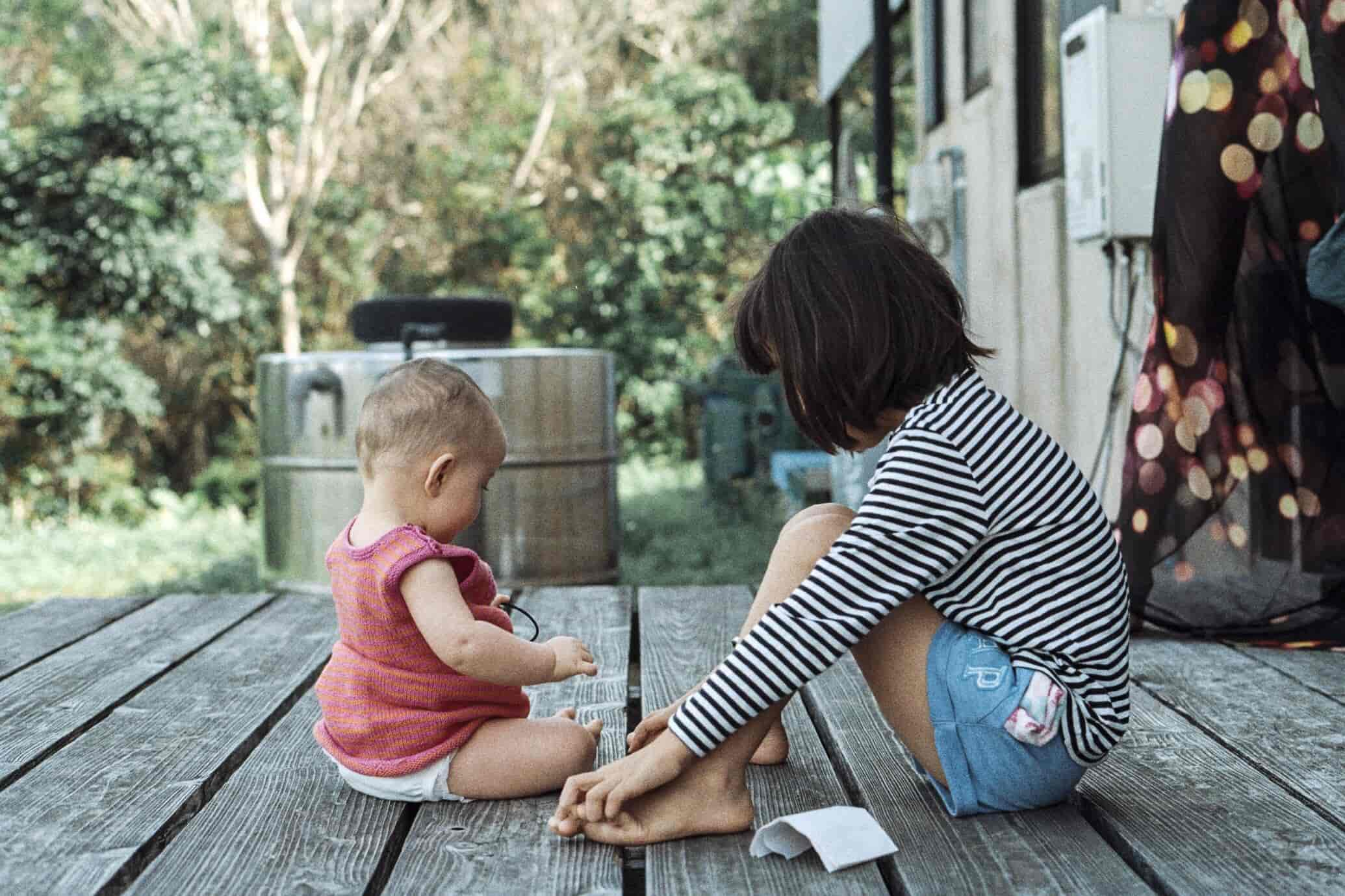 Young child and baby sitting on deck for article about why you might not need permanent life insurance