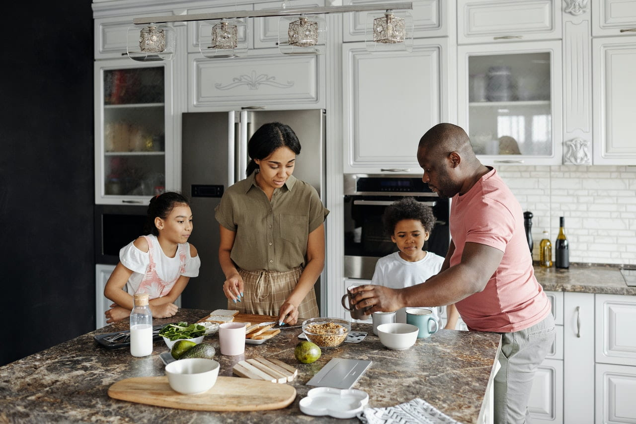 Family cooking in kitchen for article about types of life insurance