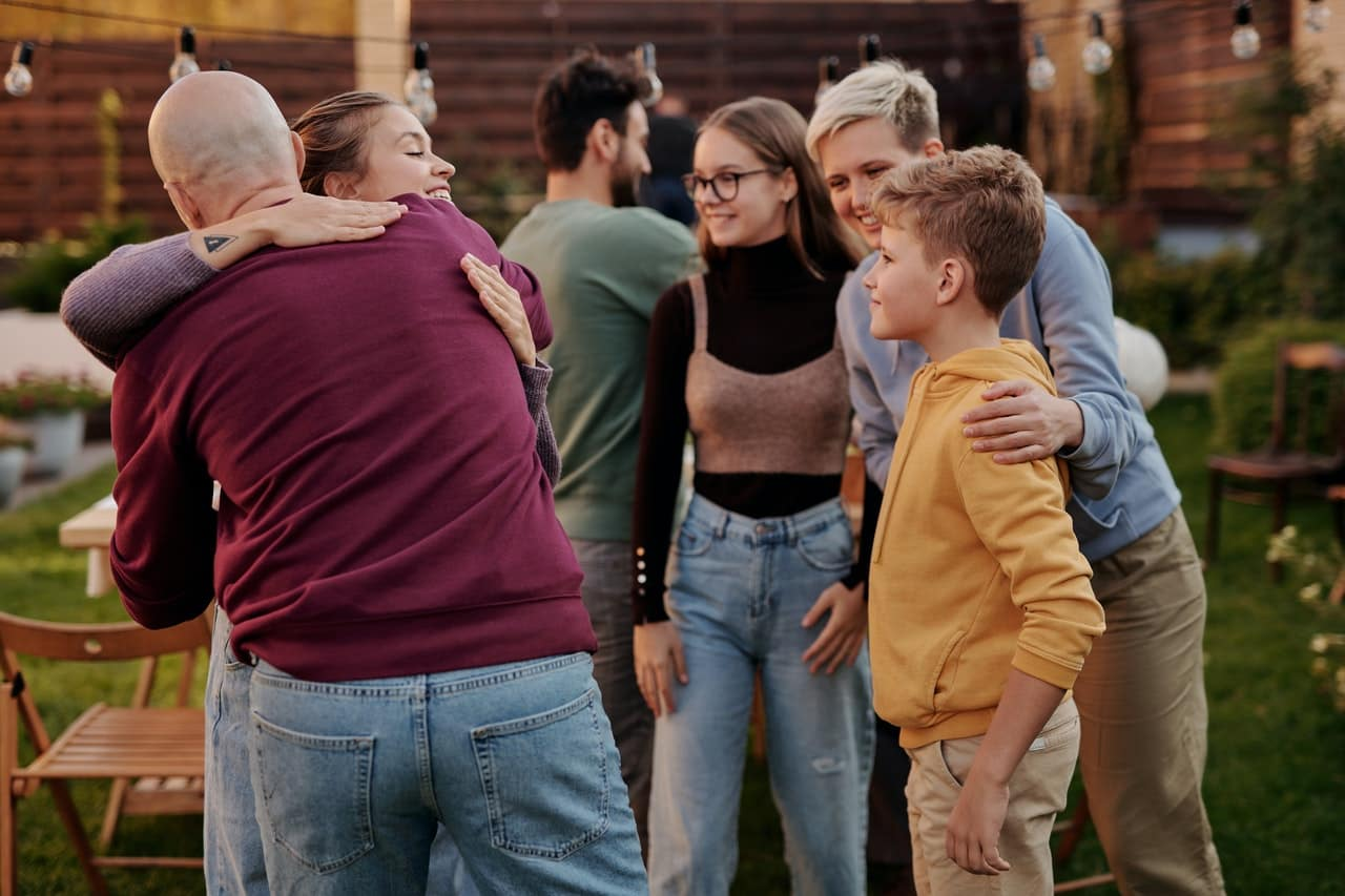 Family hugging outdoors for article on types of life insurance