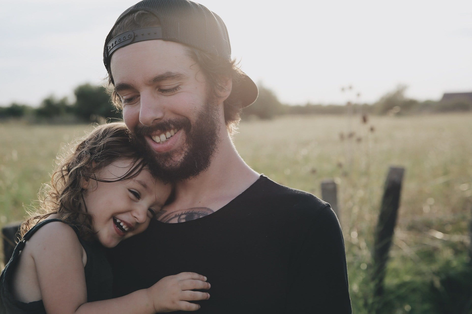 Image of father holding daughter, both smiling in a field for article about How Much Life Insurance Do I Need?