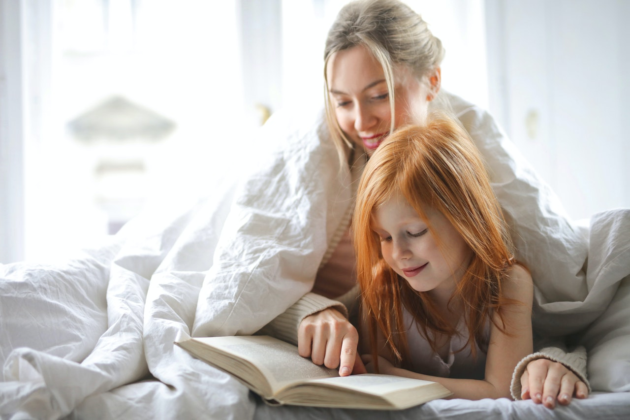 Mother and daughter reading book together while wrapped in blankets for article about whole life insurance Canada