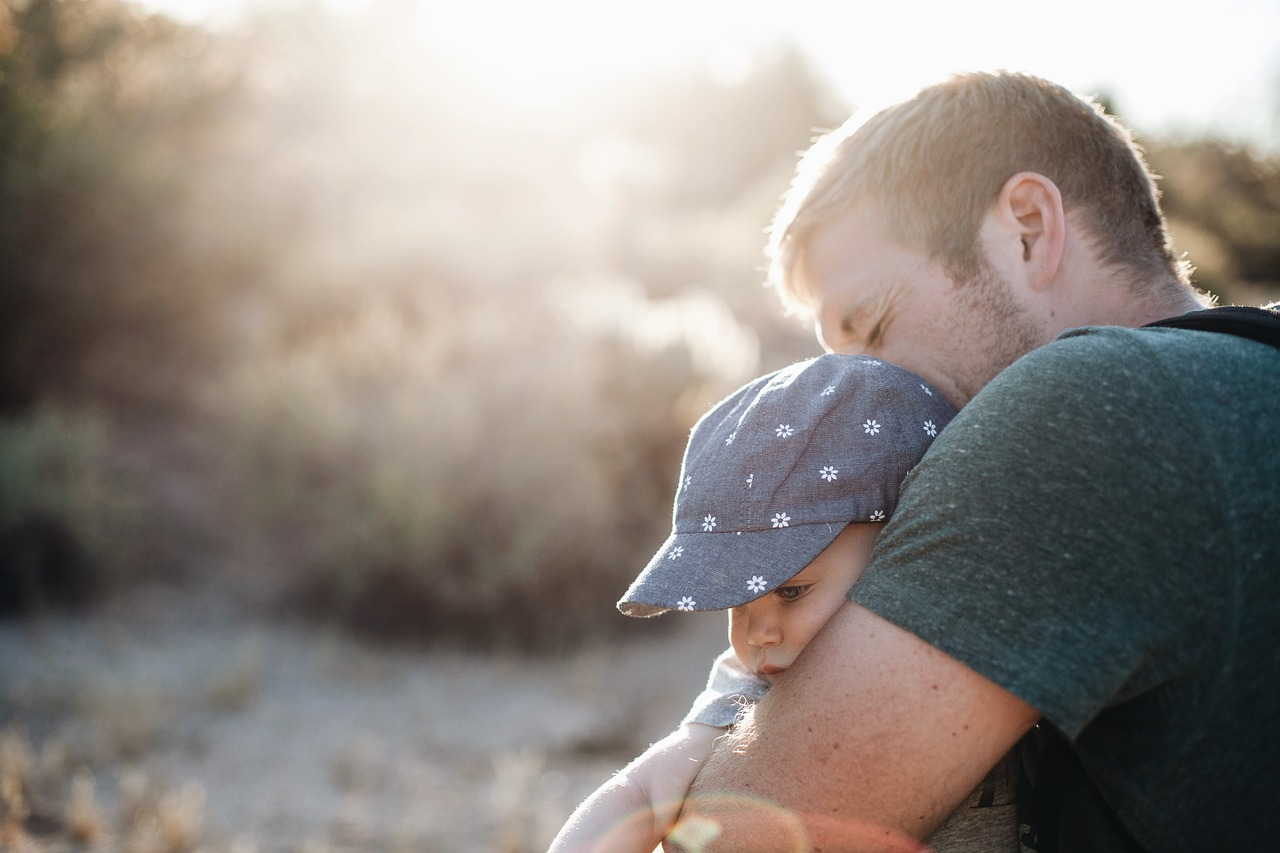 Father holding infant son for article titled What is Life Insurance