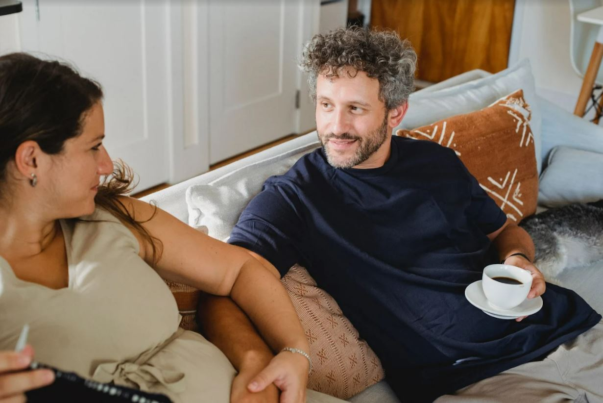 Pregnant couple on couch for article titled How Much Does Life Insurance Cost in Canada