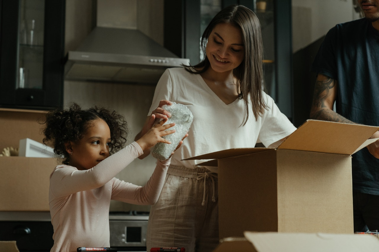 """Image of woman unpacking box in kitchen with child for article titled """"Is Mortgage Life Insurance Mandatory in Canada?"""""""