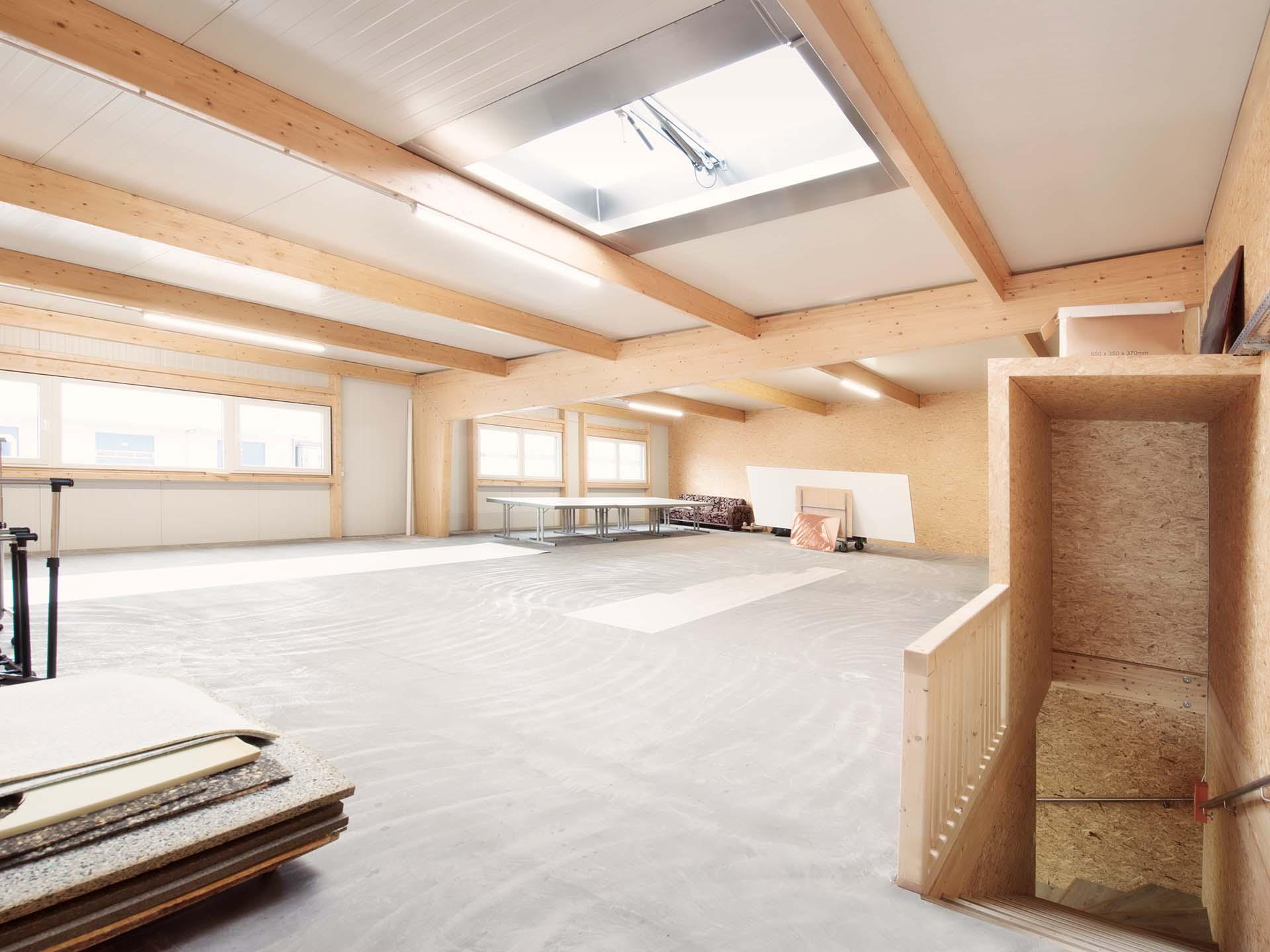 Innenansicht einer Holzhalle mit Lichtfirst.