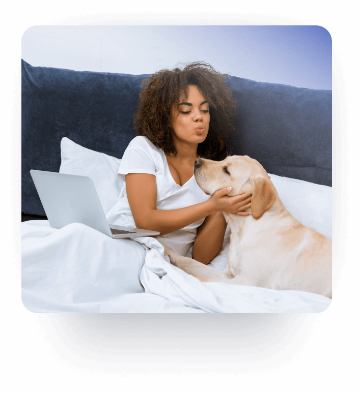 A girl in bed with her laptop and her dog searching for pet relocation