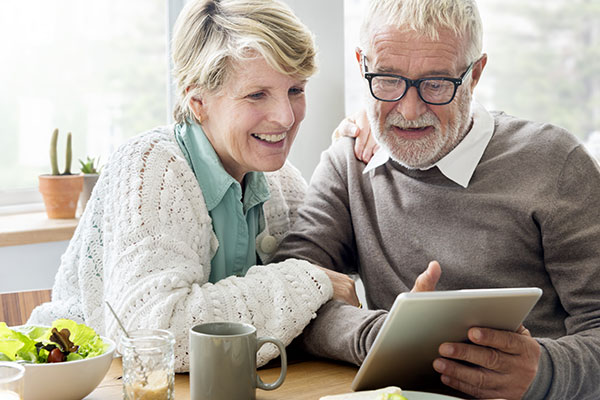 An older couple sitting at a table reviewing insurance policies.