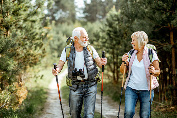 An older couple hiking on a wooded trail.
