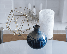 Close up of vase, candle and sculpture on a table.