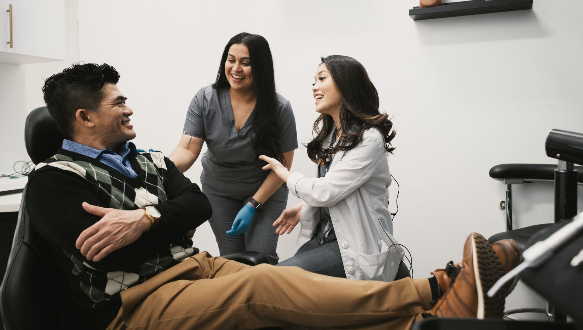Photo of Dr. Bella with an assistant working with a patient in the dental chair