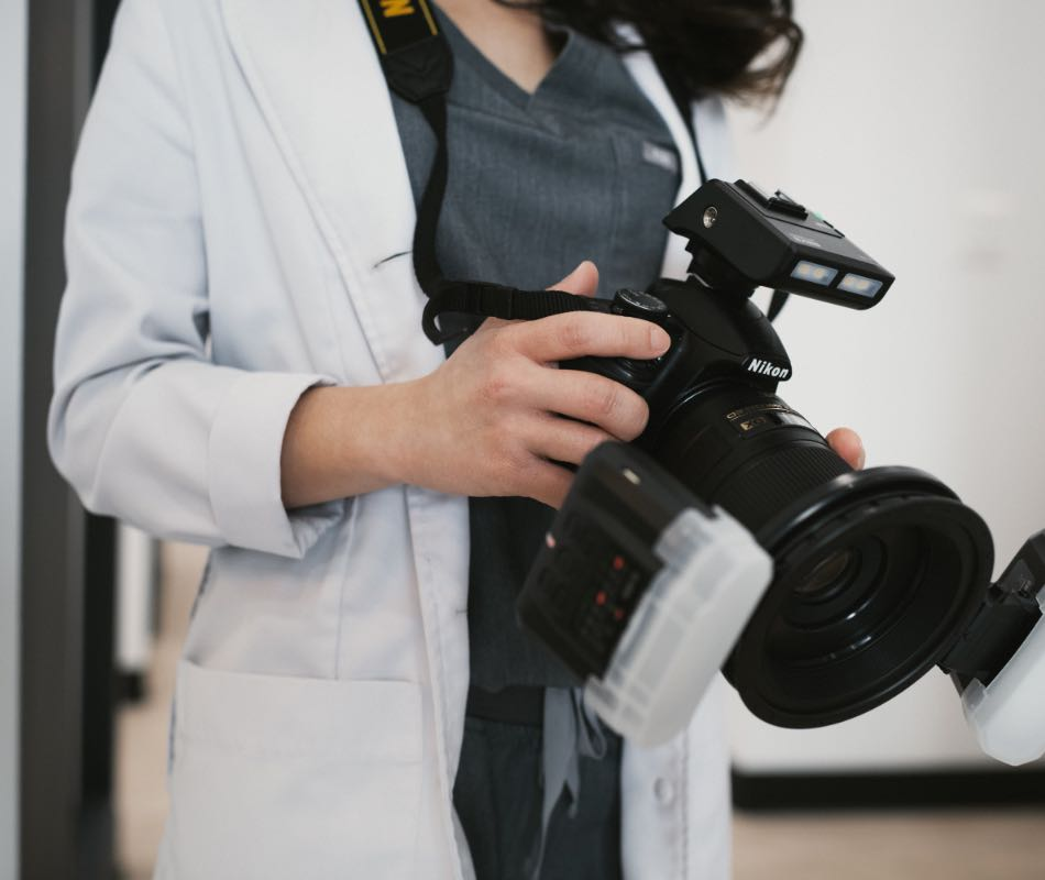 Photo of Dr. Bella holding a camera
