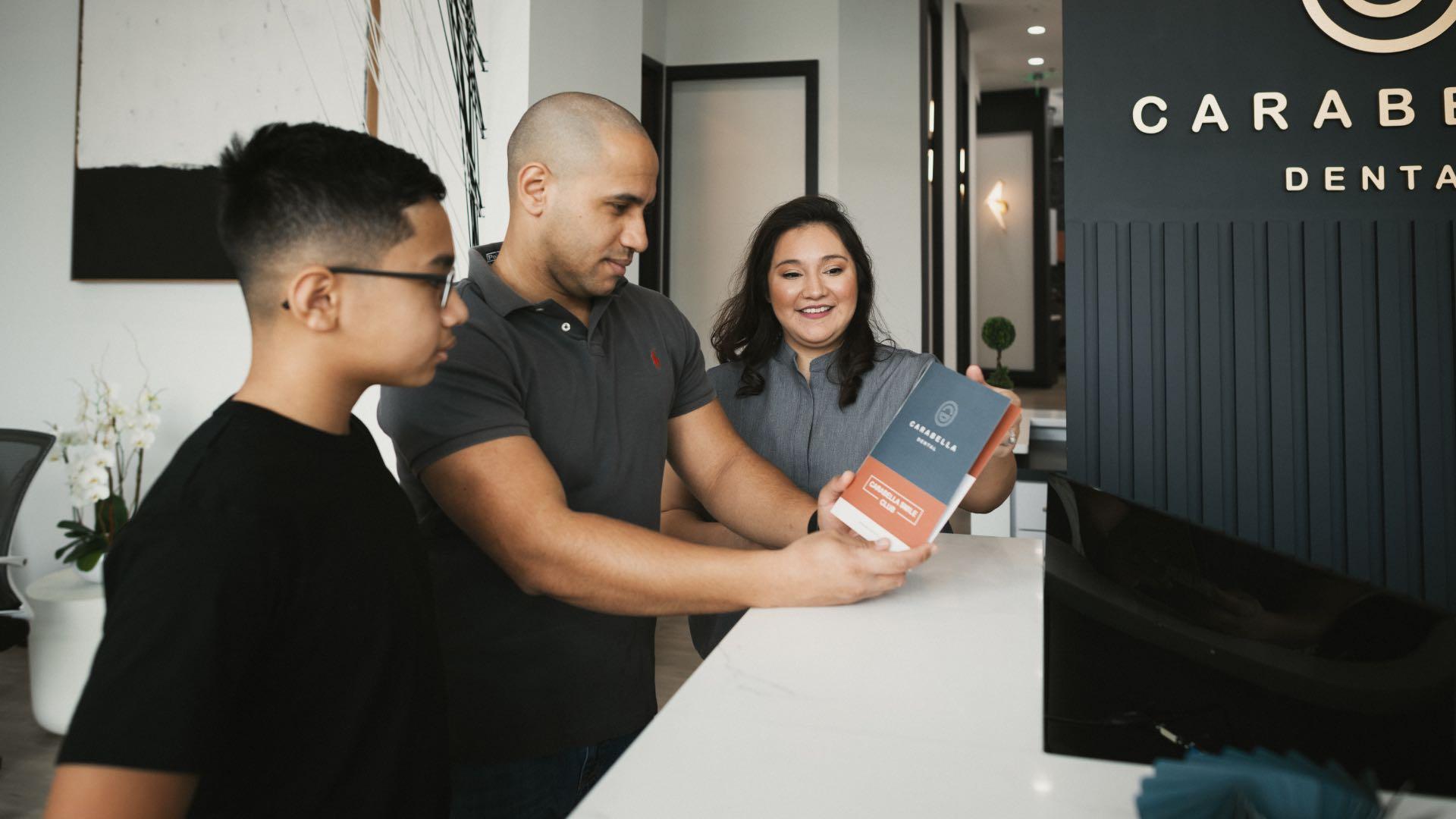 Photo of people looking at our dental membership plan brochure