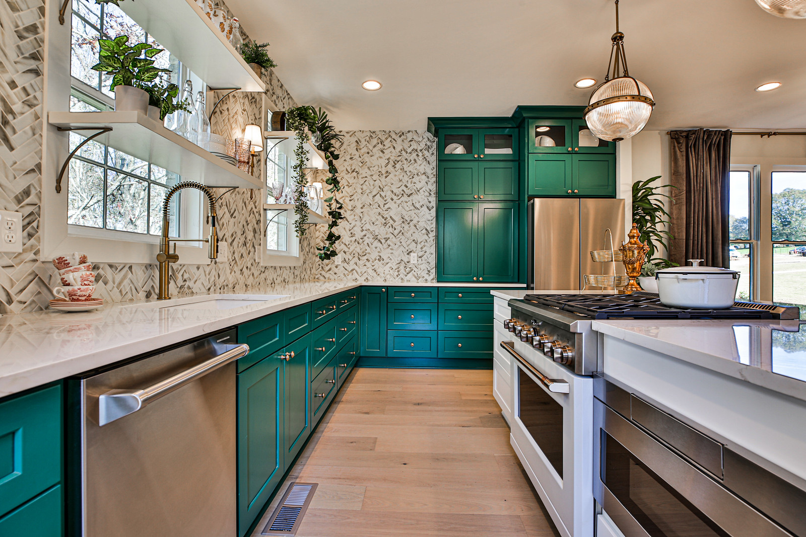 A large modern kitchen with green cabinetry.