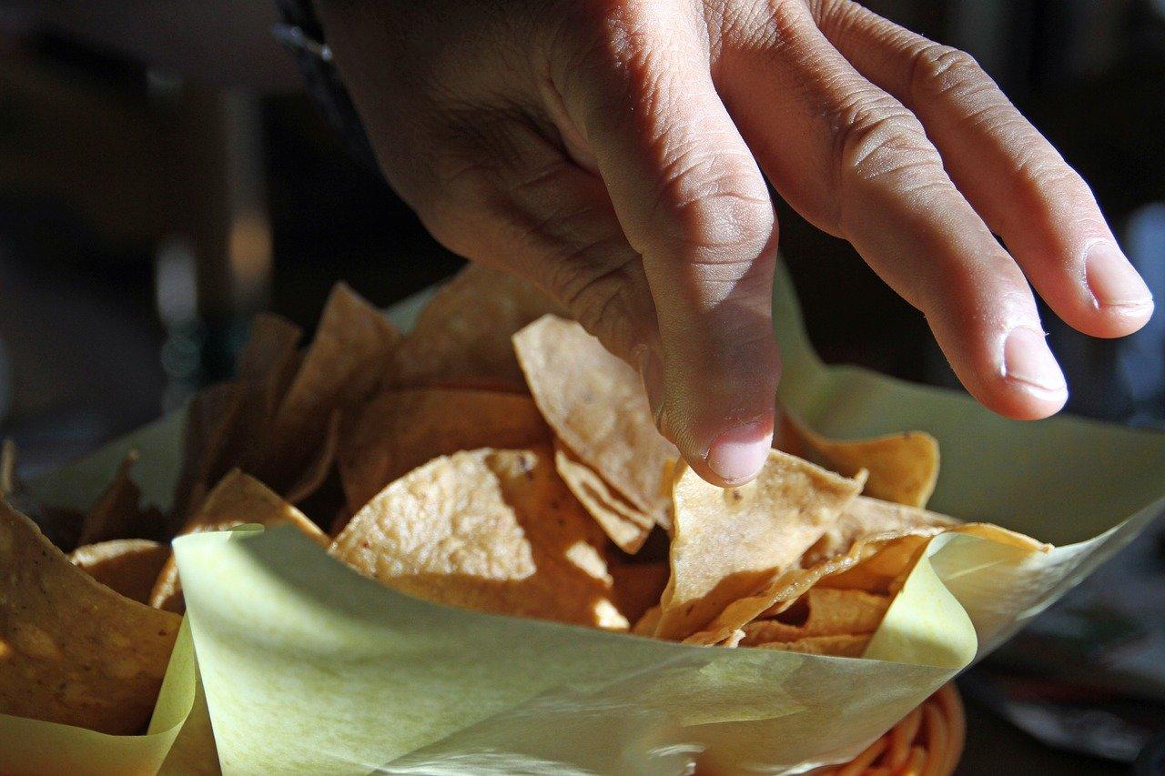 Hand picking up tortilla chips