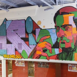 Colorful mural of a man and graffiti-style lettering