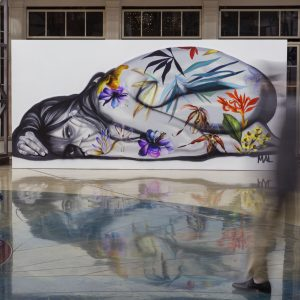Mural of a woman curled up whose skin is covered in flowers