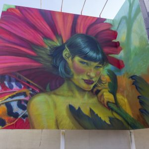Mural of a woman in front of a large flower