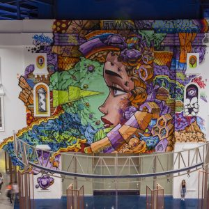 Graffiti-style mural of a woman's face profile surrounded by abstract shapes