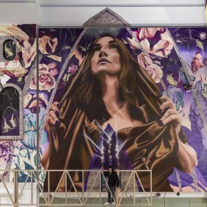 Large mural of a hooded woman surrounded by flowers