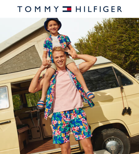 Young man with a boy on his shoulders both wearing Tommy Hilfiger floral summer clothing