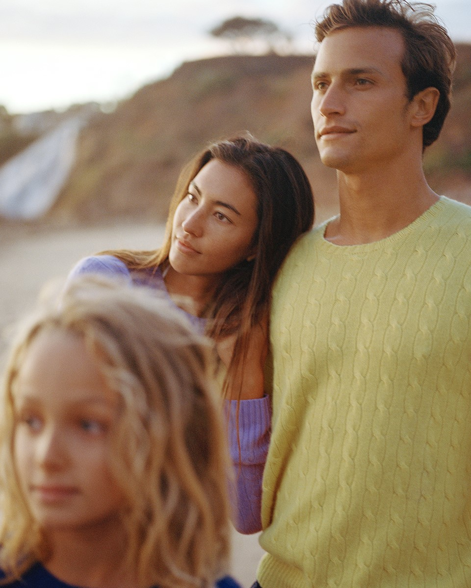 a family looking into the distance wearing polo ralph lauren sweaters at a rocky beachy terrain
