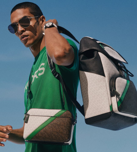 man in a green shirt wearing sunglasses with a side bag and michael kors backpack held over his shoulder.