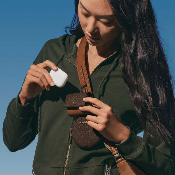 Young woman placing air pod case in a Michael Kors carrying pouch