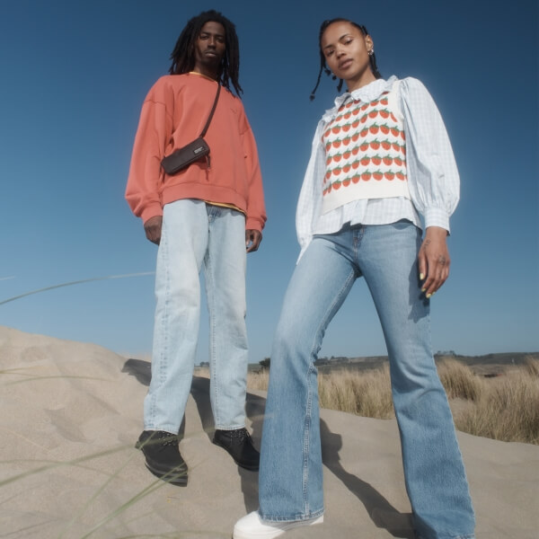 Two models wearing Levi's on a sand dune