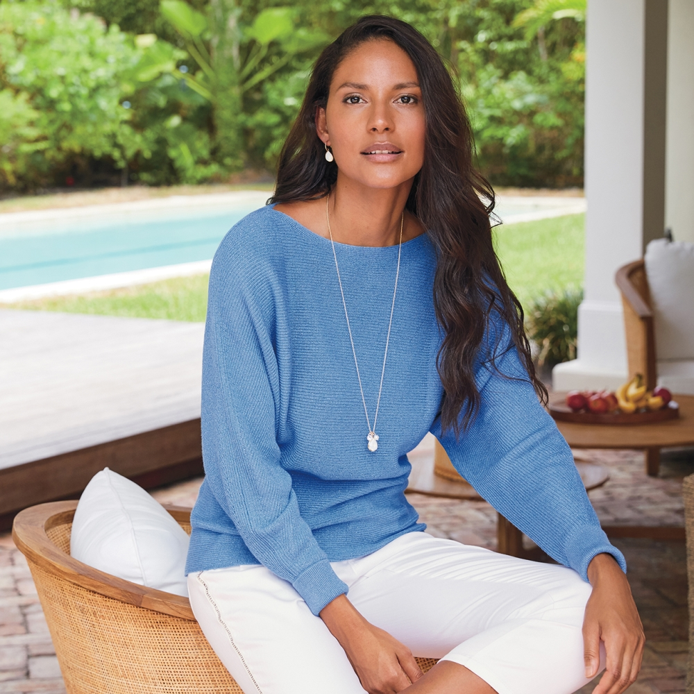 model with long brown hair wearing light blue shirt and white pants from tommy bahama