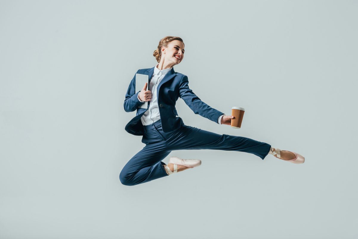 A satisfied woman after completing her moving video survey dances ballet in suit holding her coffee and her laptop