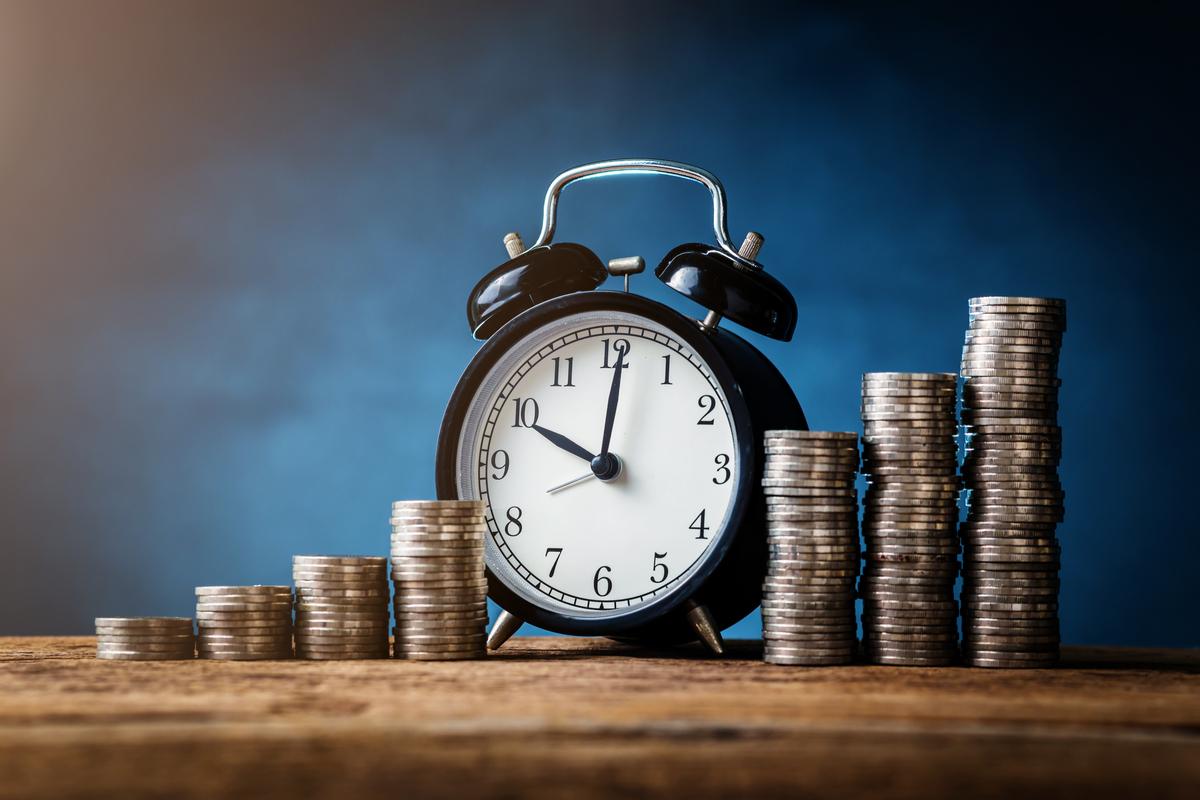 A clock ticking betweens piles of money