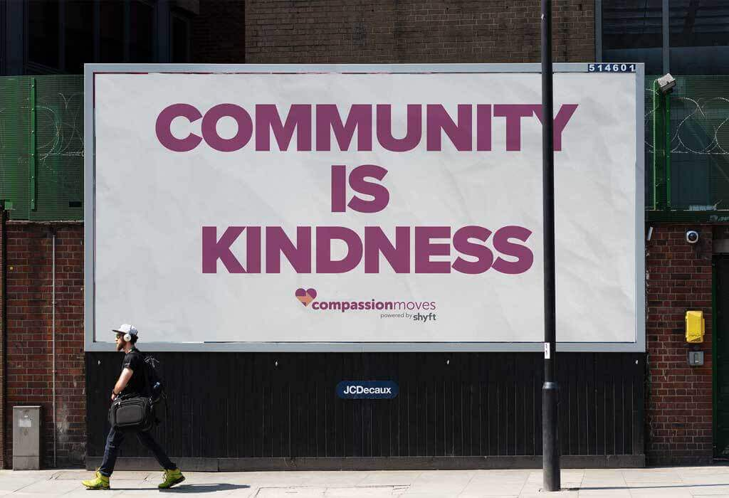 Compassion moves banner on the street saying: Community is kindness