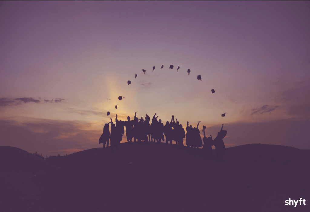College students throwing their hats while watching the sunset