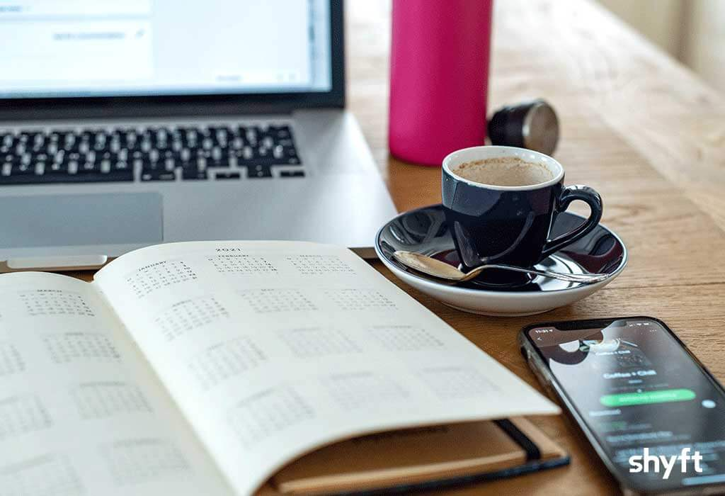 Home office desk with laptop, coffee cup, phone with a call on it and open agenda with calendar