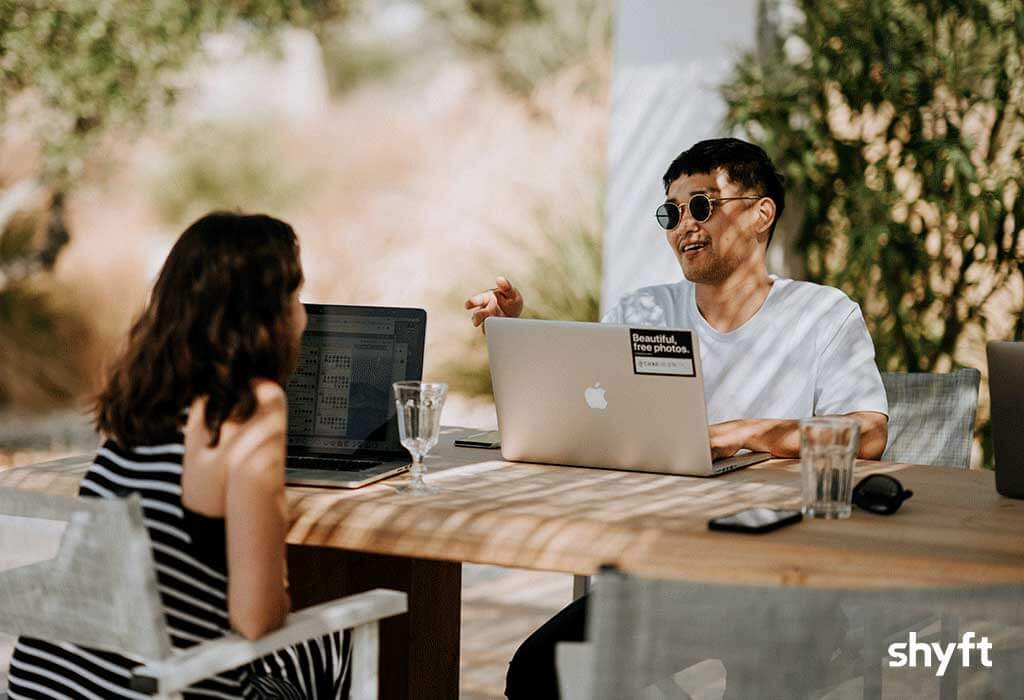 A woman and a man with laptops discussing