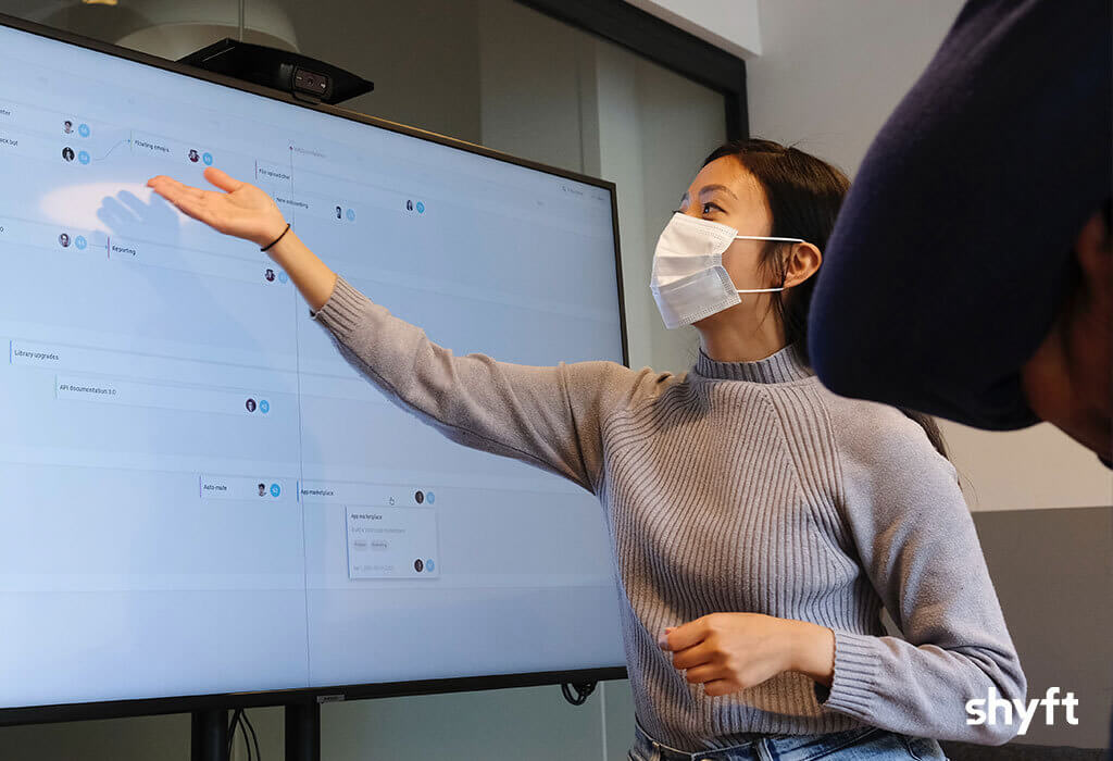 A woman presenting the changes in post-pandemic business models during a business meeting