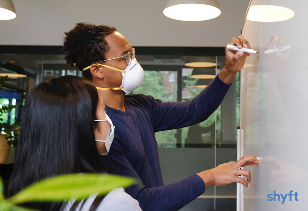 A woman and a man with masks writing on a whiteboard