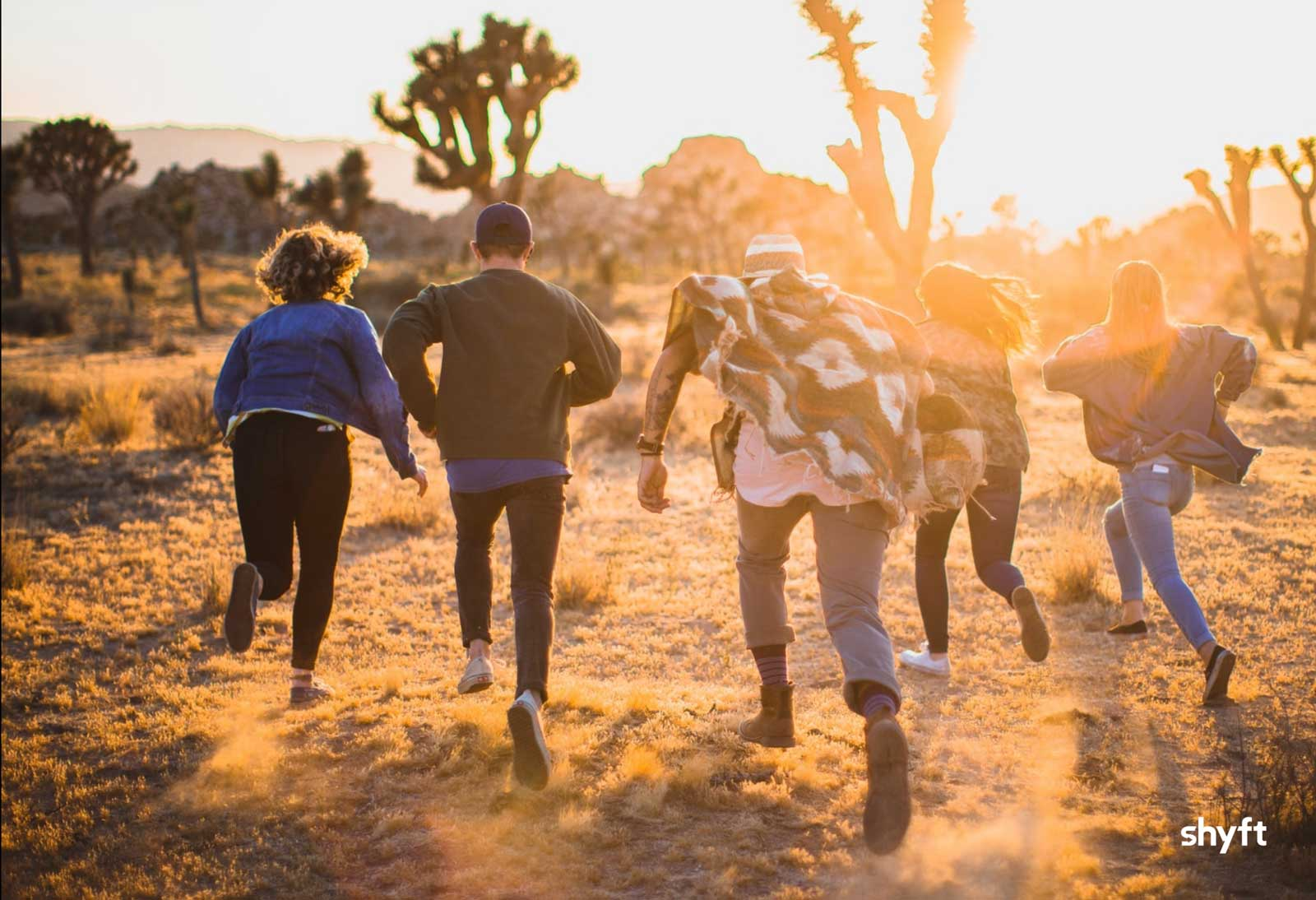 People in the wild running towards the sun and having fun outdoors